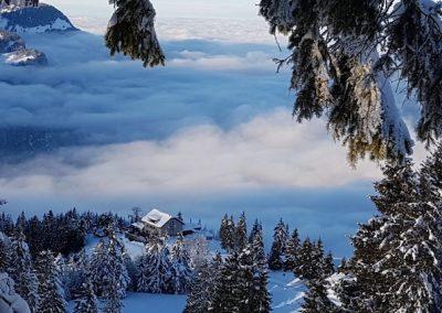 Aussicht im Winter auf Naturfreundehaus Fronalp mit Nebelmeer