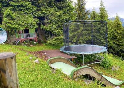 Spielplatz mit Trampolin, kleiner Rutsche und Spielhaus