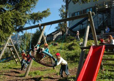 Kinder auf Spielplatz - Rutschbahn, Schaukel und Klettergerüst