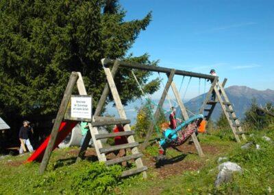 Kinder auf Spielplatz - Schaukel und Klettergerüst