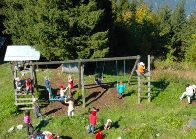 Kinder auf Spielplatz - Schaukel und Klettern