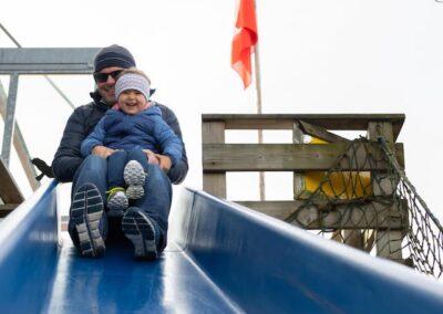Spielplatz Kind auf Riesenrutsche mit Vater